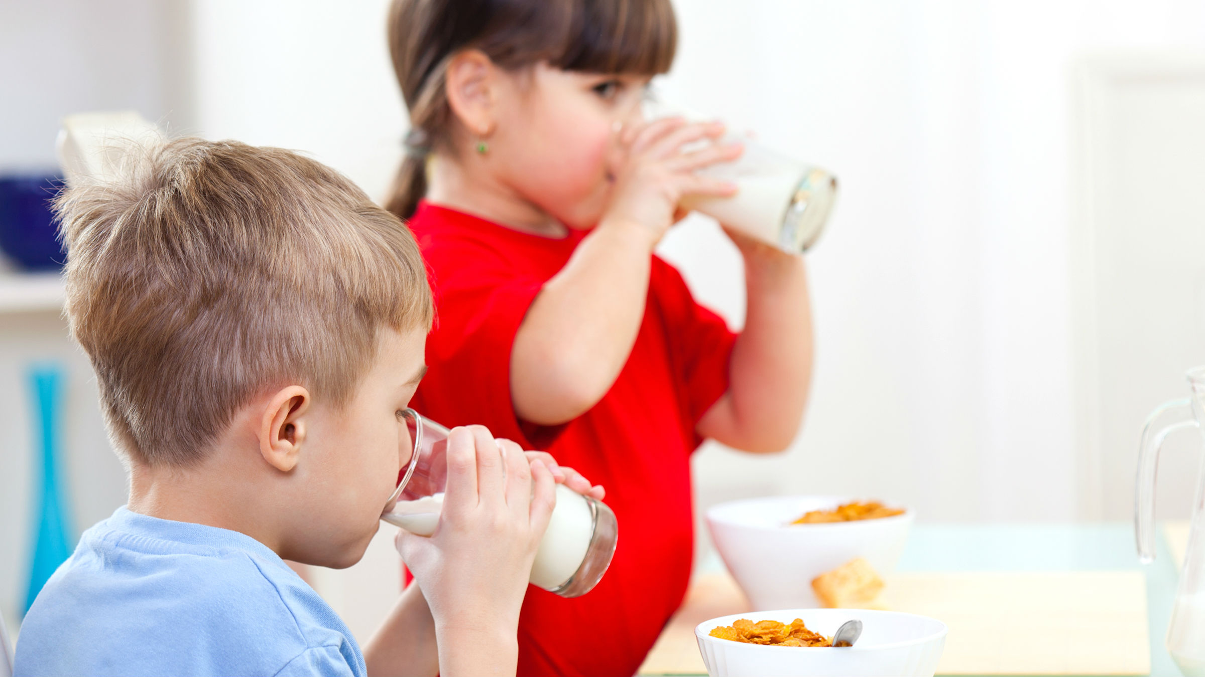 Two children drinking milk from a glass