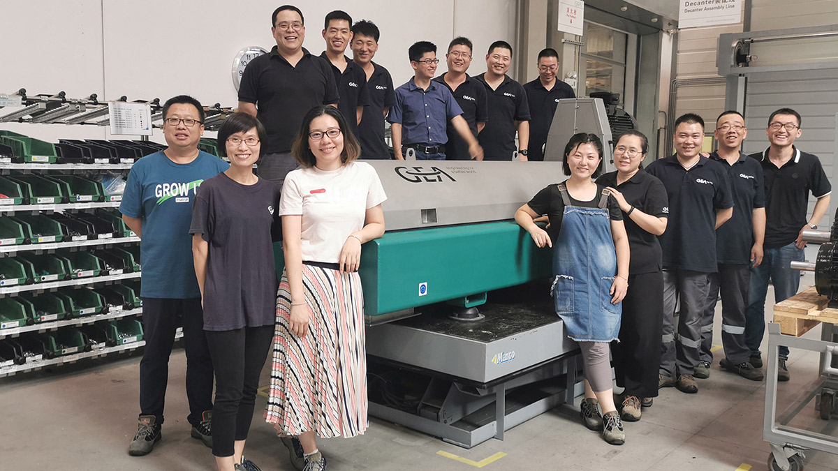 The photo shows the local Supply Chain & Production team and the Product Engineering & Development team working on a pro line decanter in Tianjin, China.